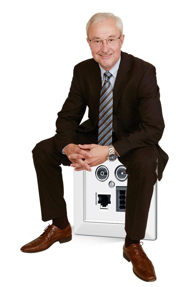 Peter Stegner sitzt auf einer überdimensional großen homeway Multimediadose
